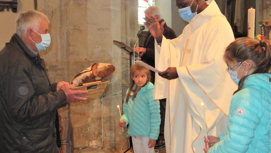 Le père Bernard Koffi bénissant une miche de pain en l'église de Luc le jeudi de l'Ascension.
