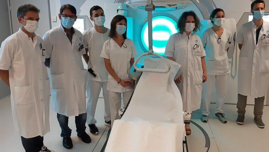 Une partie de l'équipe de radiothérapie devant le nouvel accélérateur de particules.
