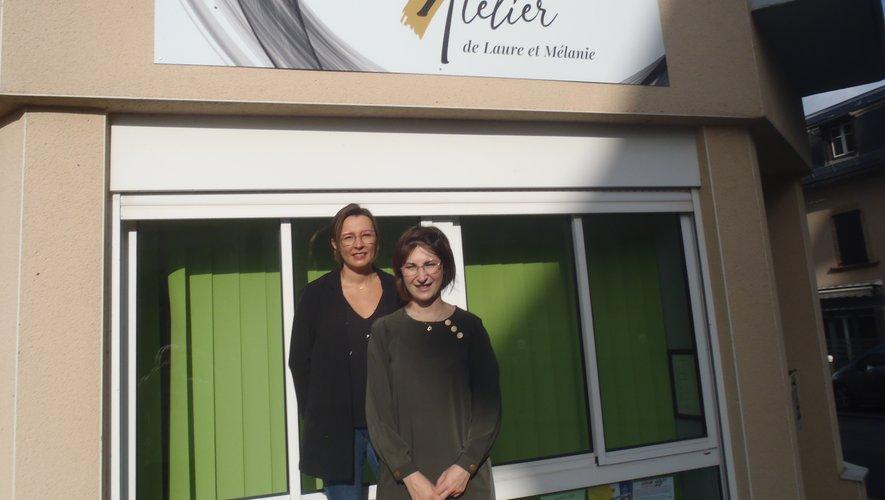 Laure et Mélanie sous l'enseigne de leur salon de coiffure.