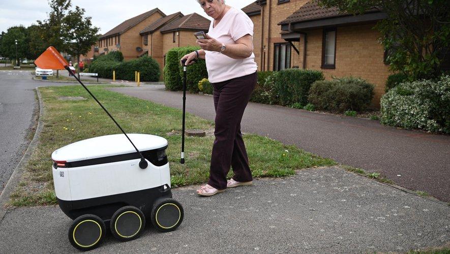 Sheila Rose, 71 ans, sort de sa maison en s'appuyant sur une canne et déverrouille le robot avec son smartphone, avant de récupérer le petit sac et les fleurs.