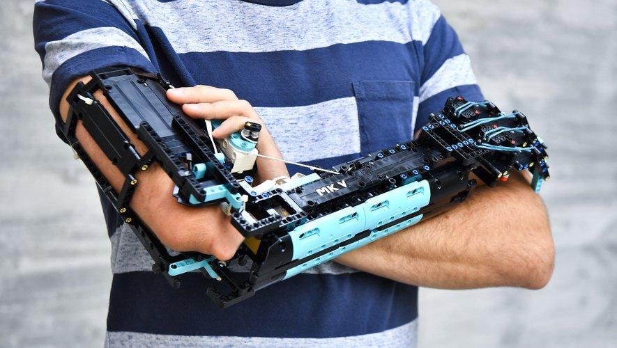 David Aguilar présente fièrement la cinquième version de sa prothèse, la MK5, un bras en Lego d'aspect robotique avec des barres bleues faisant office de doigts.